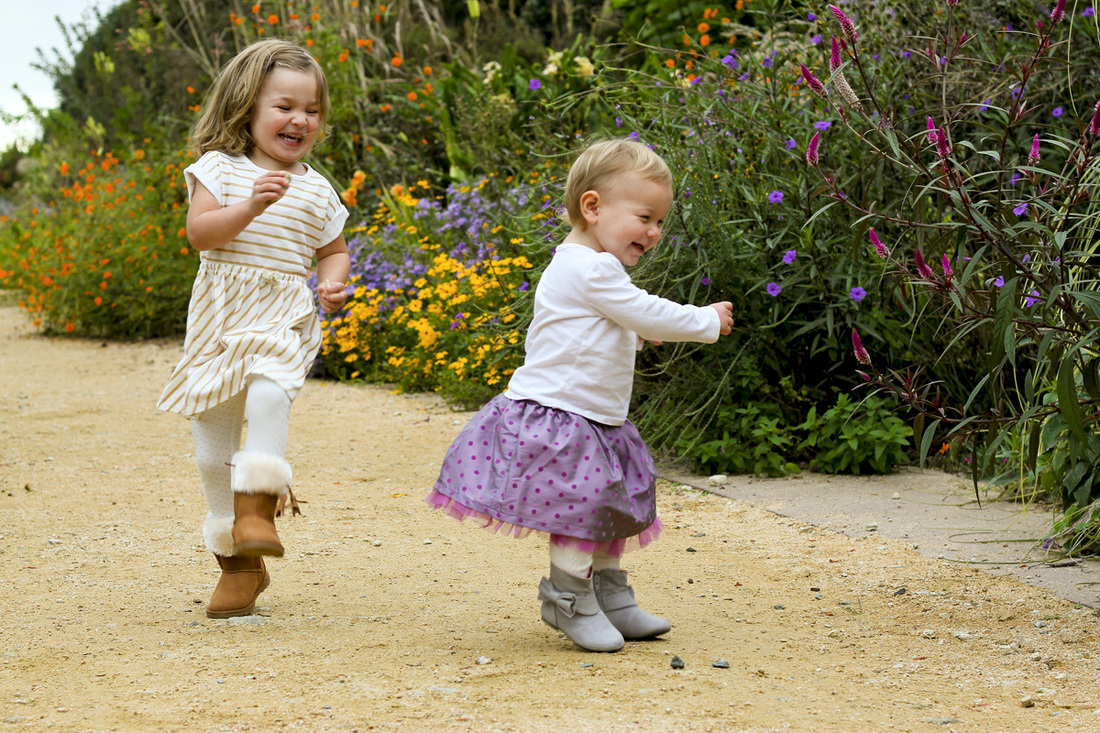 Toddler sisters dancing in the garden. By Calm Cradle Photo & Design