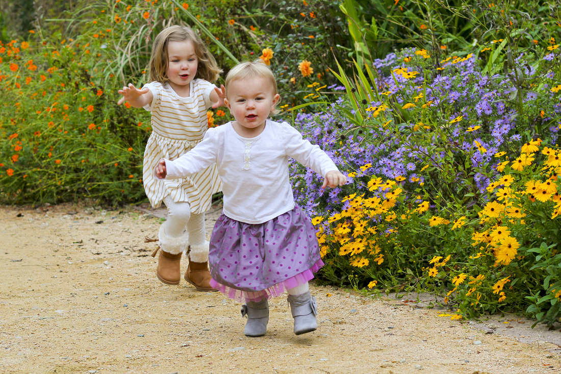 A game of sister chase in the garden. By Calm Cradle Photo & Design