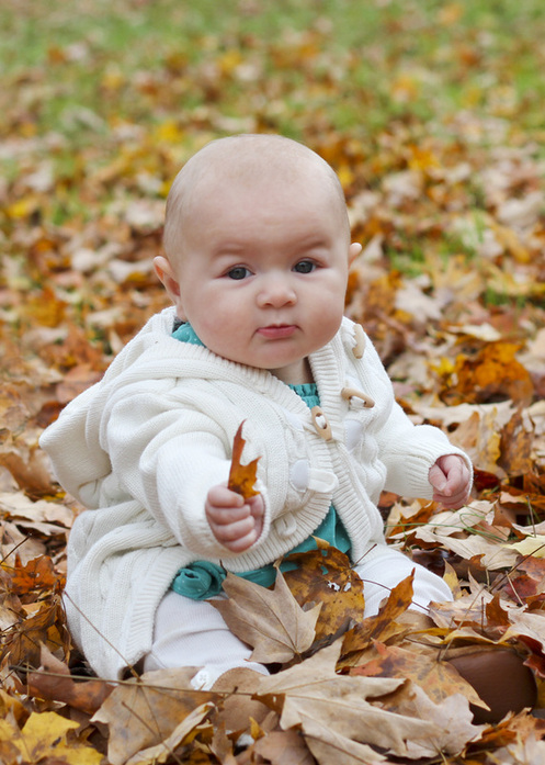 Six-month portraits: Baby in turquoise sitting in orange leaves. Calm Cradle Photo & Design