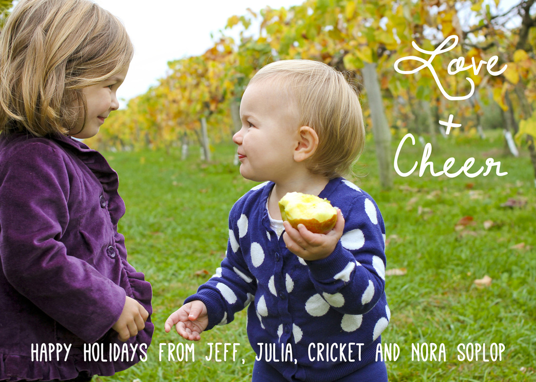 Holiday card portrait: Sisters smiling at each other in a vineyard.
