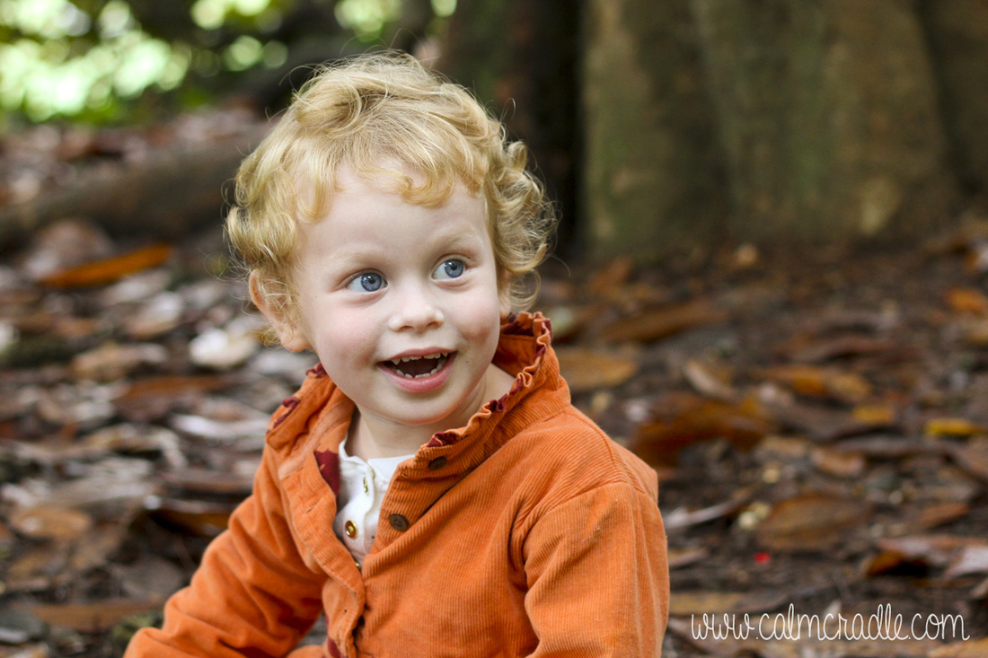 Portraits: Toddler with orange coat at the Sarah P. Duke Gardens. Durham, NC. By Calm Cradle Photo & Design