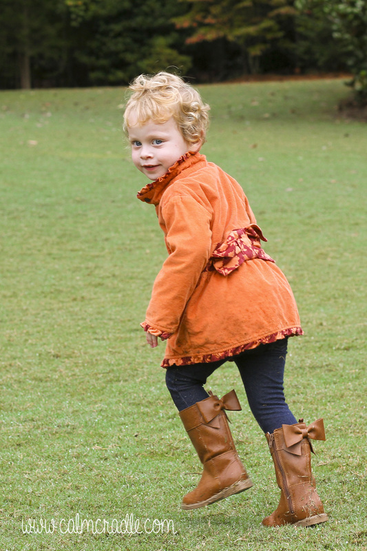 Portraits: Toddler with orange coat and curls running around the Sarah P. Duke Gardens. Durham, NC. By Calm Cradle Photo & Design