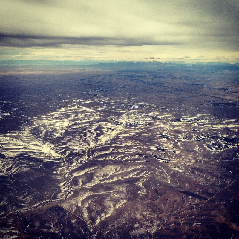 Colorado Rocky Mountains jutting up from the plains in the distance. By Calm Cradle Photo & Design