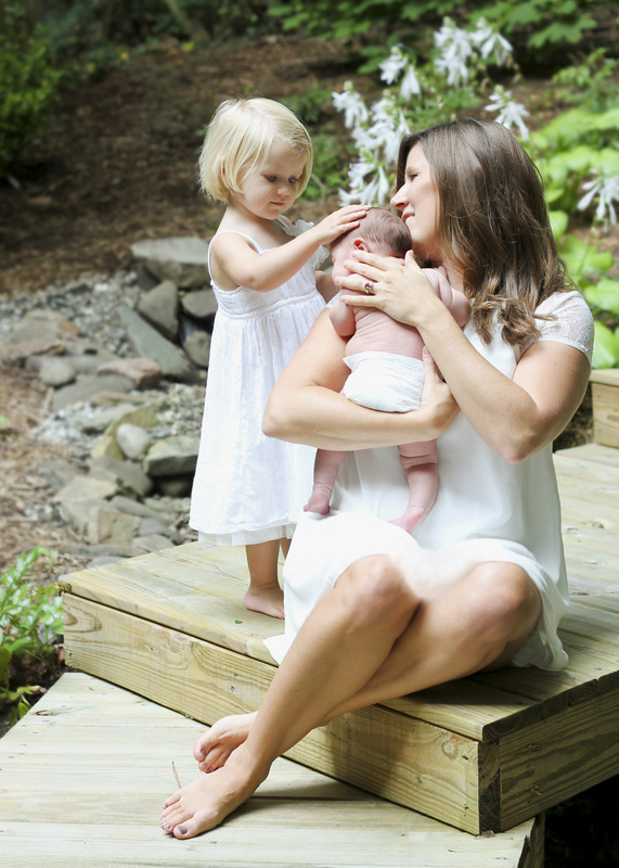 Mom with newborn and sibling outdoors wearing white. Portrait by Calm Cradle Photo & Design